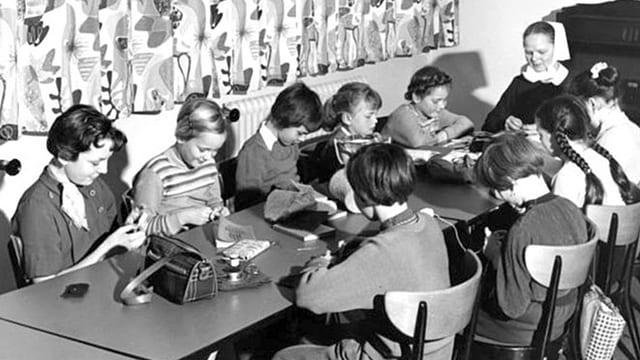Mädchen in einem Kinder- und Jugendheim beim Lesen und Stricken, beaufsichtigt von einer Ordensfrau.