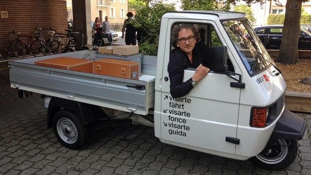 Ein Mann sitzt in einem kleinen weissen Lastwagen.