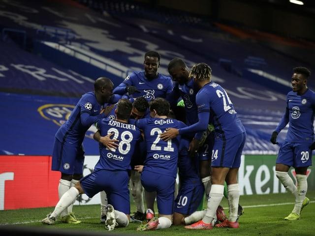Jubelnde Chelsea-Spieler vor einer leeren Tribüne.