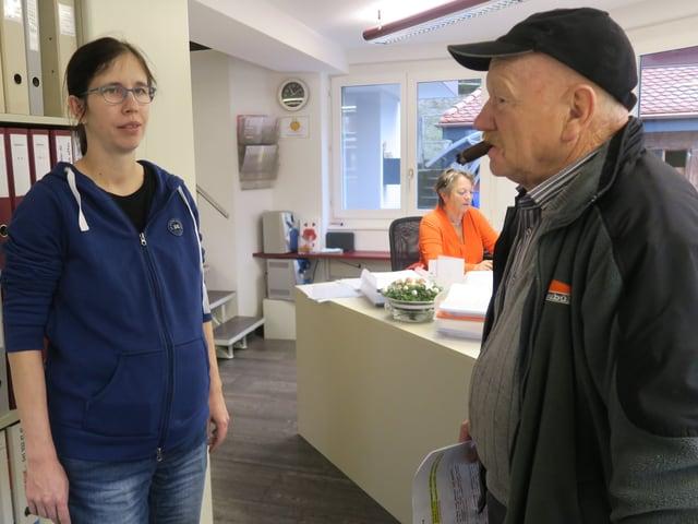 Eine Frau und ein Mann, die in einem Büro zusammen reden.