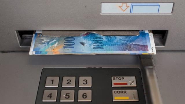 Geldscheine liegen im Schlitz des Bancomaten.