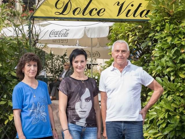 Eine ältere und eine jüngere Frau und ein Mann stehen vor dem Eingang eines italienischen Restaurants.
