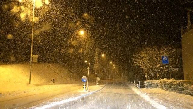 Schneefall in der Nacht, die Strasse ist schneebedeckt.