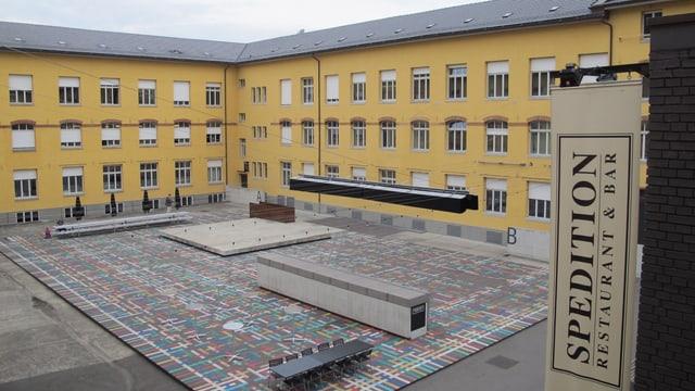 Blick in den Innenhof mit dem farbigen Kunstwerk am Boden und dem gelben Rundbau des Areals.