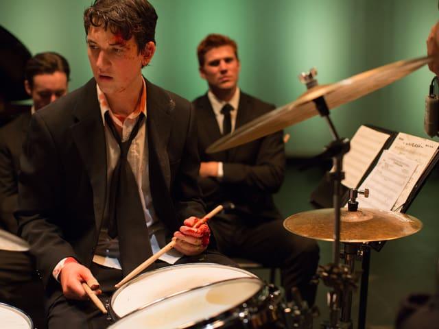 Andrew mit blutverschmierten Händen an einem Schlagzeug.