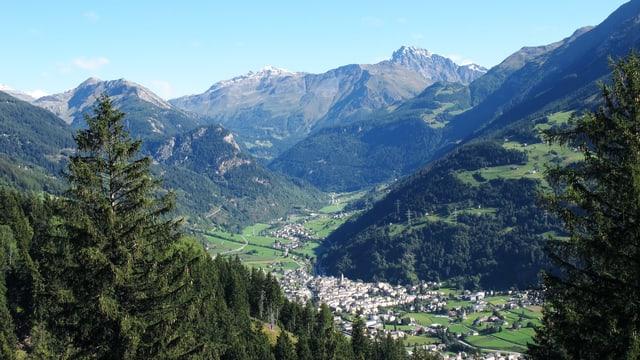 Eine idyllische Landschaft mit Dorf von oben: er ist eingesäumt durch Berge und Wälder.