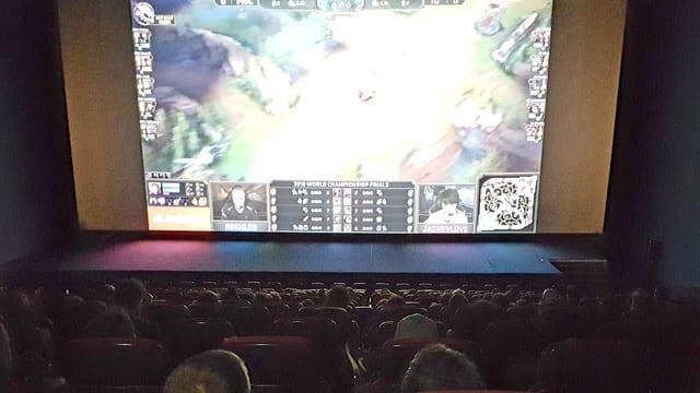 Ein grosser Kinosaal mit Leinwand, darauf das Finale von League of Legends.
