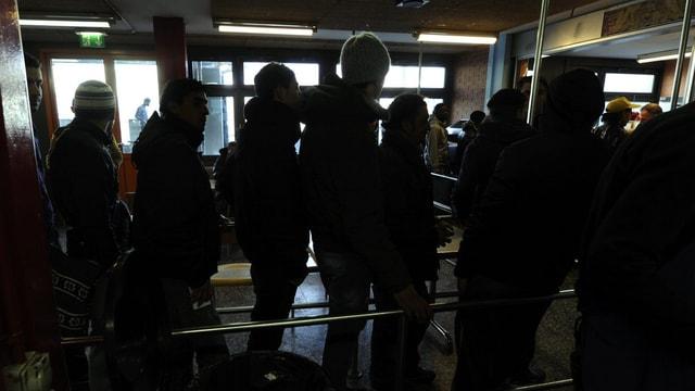 Asylbewerber im Empfangszentrum Chiasso stehen für diie Essensausgabe an.