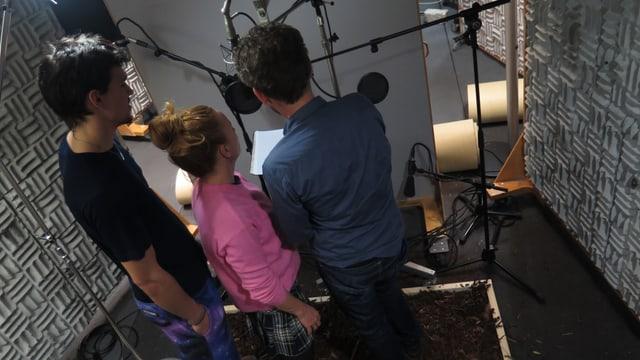 Zwei Männer, und eine Frau stehen vor einem Mikrophon