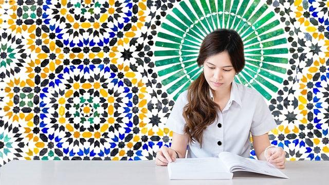 Eine Frau sitzt an einem Tisch und liest in einem Buch. Auf der Wand hinter ihr sind bunte Ornamente gemalt.