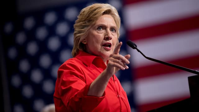 Hillary Clinton spricht ins Mikrofon und zeigt dabei mit dem Finger.