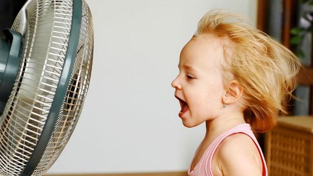 Ein kleines Mädchen steht vor einem laufenden Ventilator.