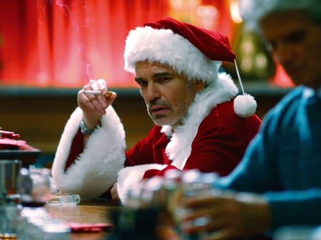 Billy Bob Thornton im Weihnachtsmann-Kostüm, er sitzt schlecht gelaunt und rauchend an einer Bar.