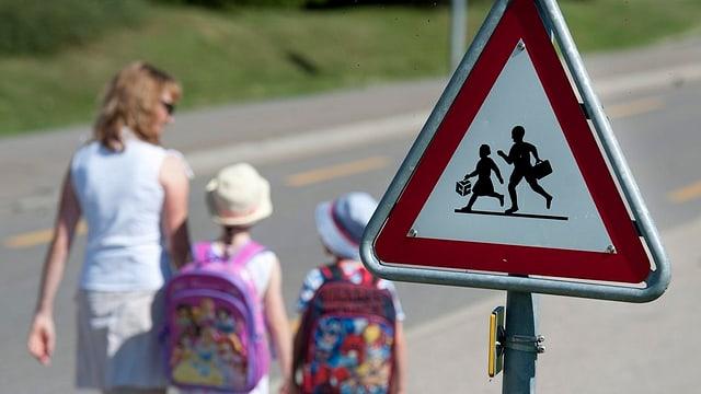 Kinder und ihre Mutter auf dem Schulweg.