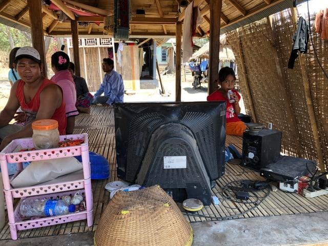 Personen schauen auf einen Fernseher, der unter einem Bambus-Zelt untergebracht ist.