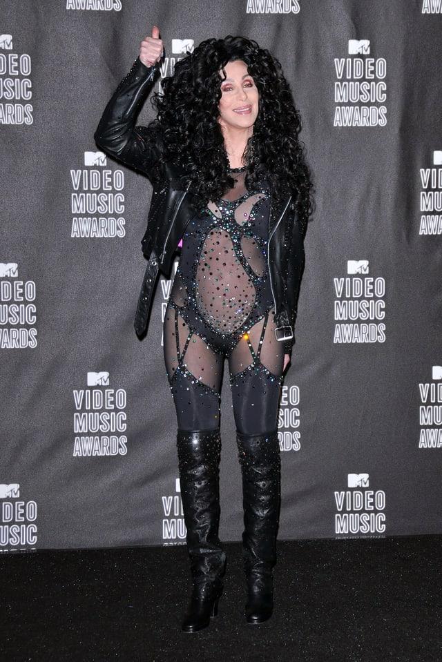 Cher posiert auf dem roten Teppich und streckt ihren Daumen in die Höhe.