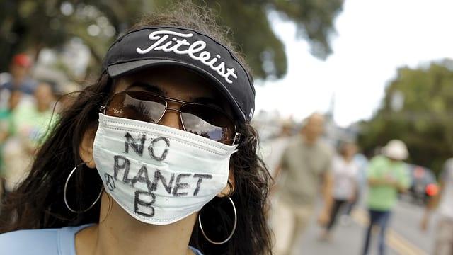 Eine Demonstrantin trägt einen Mundschutz mit der Aufschrift «No Planet B»