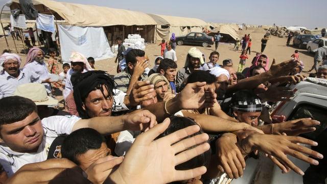 Flüchtlinge strecken Helfern die Hände entgegen.