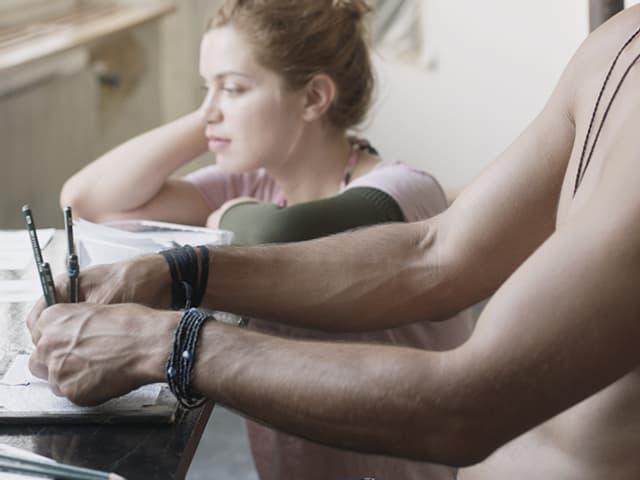 Zeichnende Männerhände im Vordergrund, Liliane Amuat in der Unschärfe im Hintergrund.