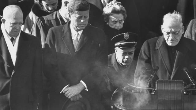 Feiner weisser Rauch steigt auf der linken Seite des Rednerpultes auf, Kennedy schaut interessiert