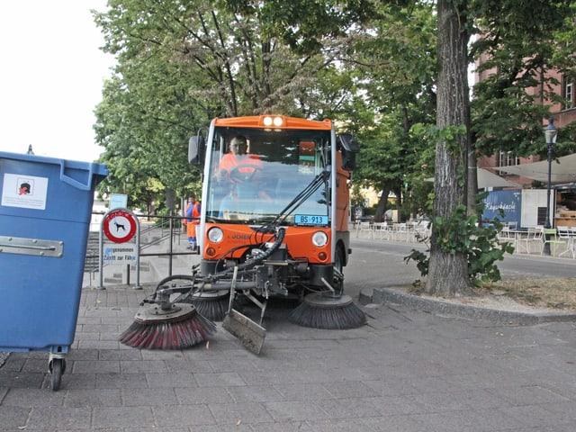 Ein oranger Putzwagen fährt herum.