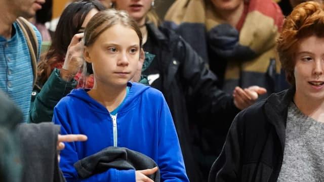 Greta Thunberg umringt von anderen Personen.