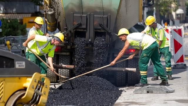 Strassenbauarbeiter verteilen Asphalt