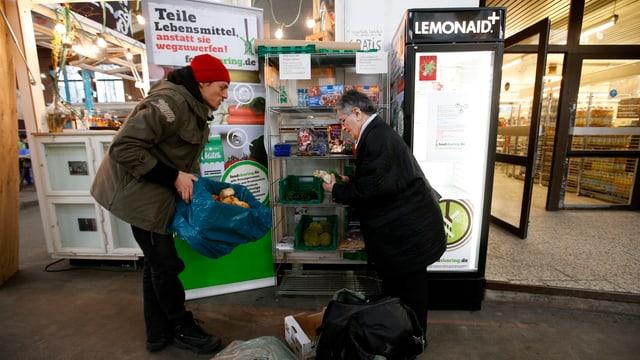 Ein junger Mann und eine ältere Frau stehen vor einem offenen Kühlschrank, der vor einem Supermarkt platziert ist.