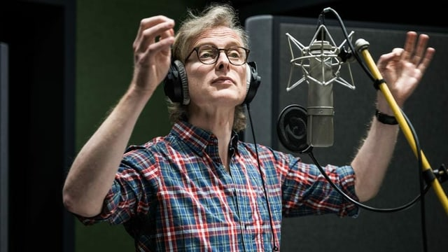 Synchronsprecher Martin Ostermeier vor einem Mikrofon während den Aufnahmen im Studio.
