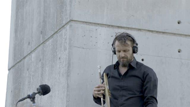 Der Berner Trompetenspieler steht unter einer Autobahnbrücke und horcht nach Geräuschen.