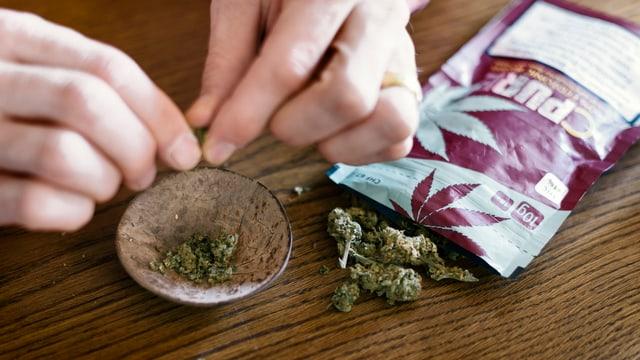 Purtret d'ina persuna che fa dapart ina troccla da cannabis medicinal en in cup.