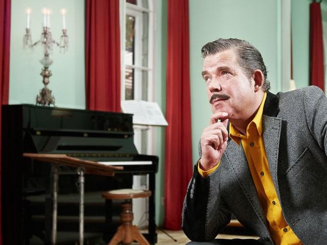 Boris Blank in einem grauen Anzug und einem gelben Hemd.