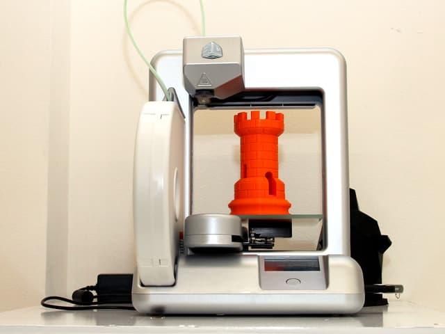 Ein 3D-Drucker mit einem gedruckten roten Turm aus Plastik.