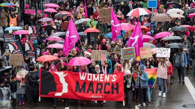 Demonstration von Frauen in Zürich, mit Transparent und pinkfarbenen Regenschirmen.