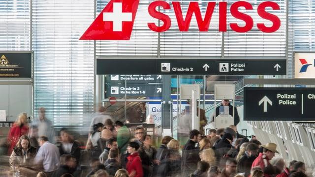 Swiss-Logo am Flughafen Kloten mit Passagieren.