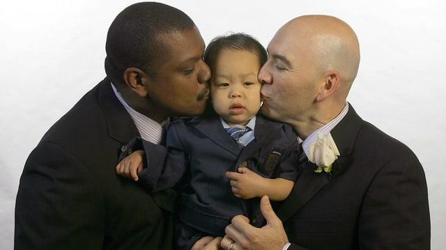 Zwei Männer küssen ein Kleinkind auf ihren Armen.