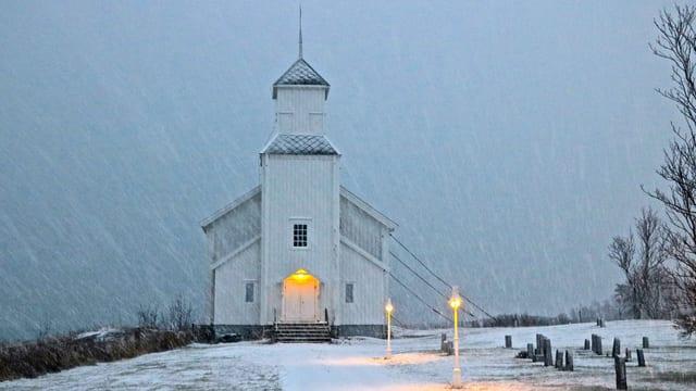 Weisse Holzkirche im norwegischen Schneesturm.
