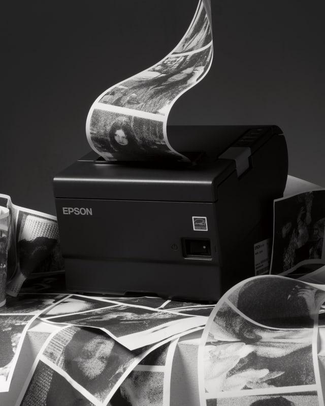 Aus einem kleinen Drucker werden auf einem langen Papierstreifen viele Fotos in Schwarzweiss gedruckt