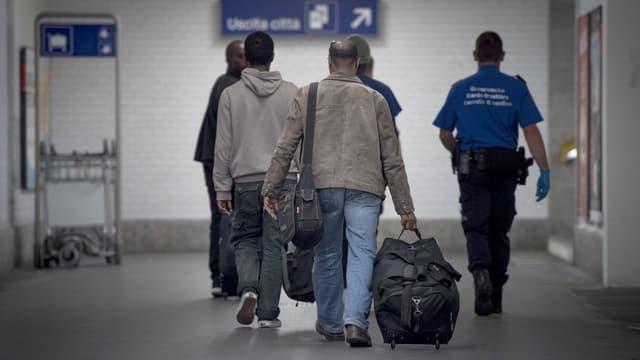 Eine Gruppe Migranten von hinten geht zusammen mit einem Grenzwächter eine Bahnhofsuntrführung entlang.