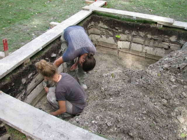 Zwei Personen sitzen in einer kleinen Grube.