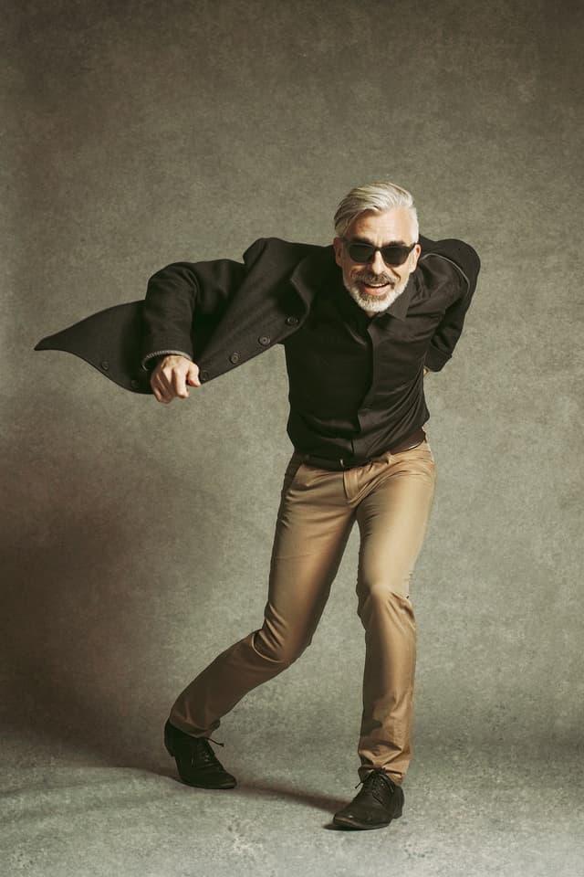 Ein Mann mit grauen Haaren und Sonnenbrille macht eine lustige Pose für die Kamera.