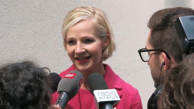 Eine Frau in einem pinken Kleid, welche Journalisten mit Mikrofon Auskunft gibt.
