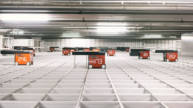 Rote Roboter-Wagen suchen in einem modernen Warenlager nach Artikeln.