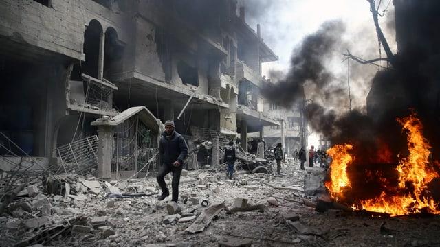 Trümmer und Brände, dazwischen Menschen.