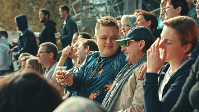 Im Fokus: Zwei Männer sitzend auf einer Fussballtribüne. Einer ist jung, der andere älter. Der ältere Mann trägt Mütze und Sonnenbrille. Beide lächeln.