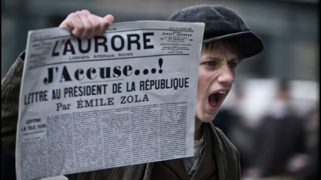 Zeitungsjunge hält schreiend eine Zeitunng in die Luft, auf der der Titel «J'accuse!» zu lesen ist.