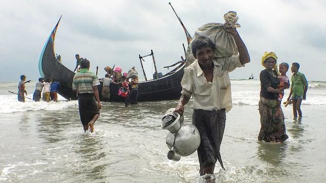 Geflüchtete im Meer beim Ausladen eines Schiffs