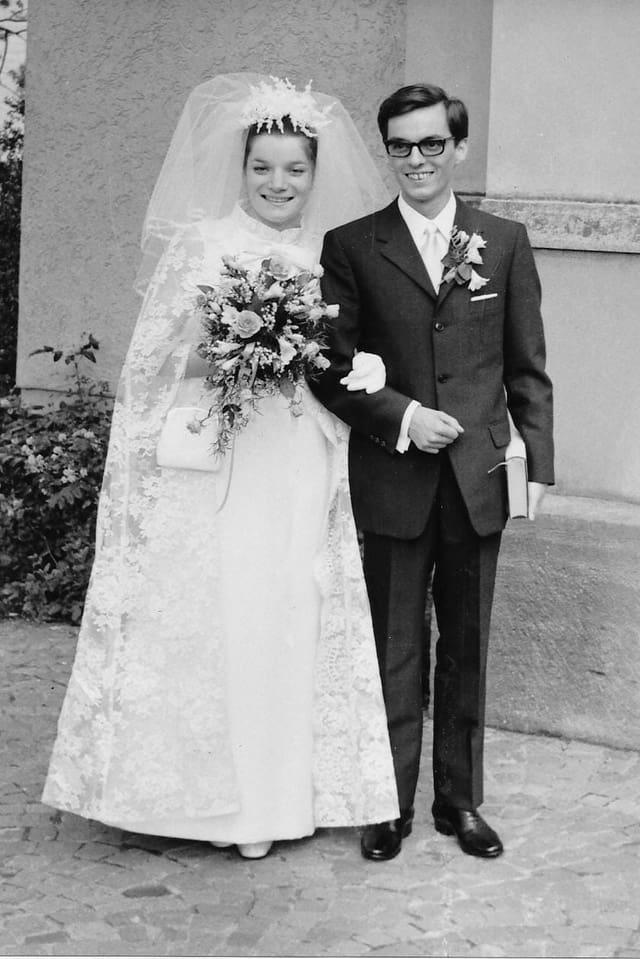 Ein Schwarzweiss-Foto eines Brautpaars. Sie im weissen Kleid mit Spitzen-Umhang und Schleier, er im dunklen Anzug mit Blumen im Knopfloch.