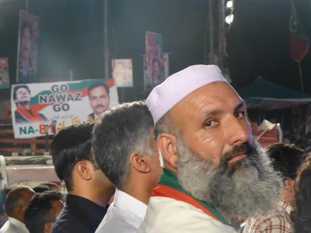 Hinten ein Schild: «Go, Nawaz, Go», vorne ein Mann mit einer weissen Kopfbedeckung und einem Bart.
