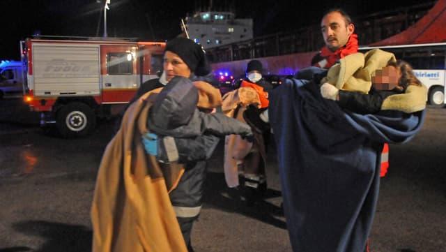 Eine Frau mit ihren Kindern und einem Helfen kommt von der Fähre.